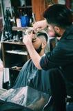 El corte de pelo del pelo de la barbería del peluquero trabaja mejor imagen de archivo libre de regalías