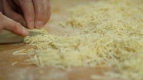 El corte de tallarines rueda en tabla de cortar por las manos cerca para arriba metrajes