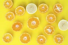 El corte fresco da fruto las frutas cítricas en un fondo amarillo Fotos de archivo