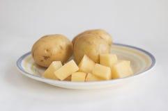 El corte y la patata entera en una placa Fotografía de archivo