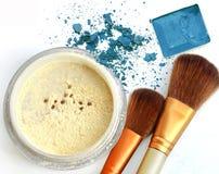 El cosmético compone el polvo en caja del círculo y se ruboriza, sombreador de ojos azul machacado como fondo Imagen de archivo