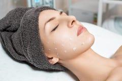 El cosmetólogo aplica la crema de cara en mujer joven hermosa en salón del balneario cuidado de piel cosmético del procedimiento Imagenes de archivo