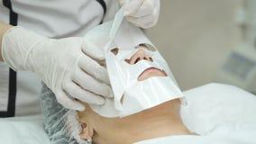 El cosmetólogo aplica la máscara facial a la piel del ` s de la muchacha almacen de video
