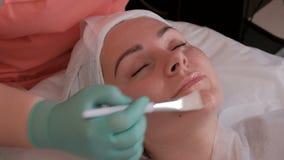El cosmetólogo aplica un gel o una crema de alimentación a la cara de una mujer joven Muchacha hermosa en el cosmetological metrajes