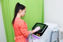 El cosmetólogo caucásico de la muchacha ajusta el dispositivo según el retiro del pelo con un laser Dispositivo cosmético del equ fotos de archivo
