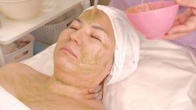 El cosmetólogo con un cepillo aplica una máscara de algas o del kiwi verde en la cara de una mujer asiática Muchacha musulmán con metrajes