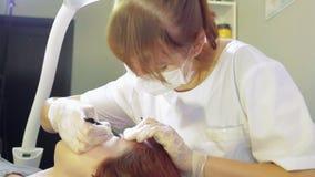 El cosmetólogo corrige las cejas del cliente con pinzas y un cepillo almacen de metraje de vídeo
