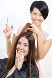 El cosmetólogo corta el pelo de la mujer en el peluquero Foto de archivo libre de regalías