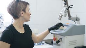 El cosmetólogo da vuelta en el dispositivo electrónico antes del procedimiento cosmético, cámara lenta almacen de metraje de vídeo