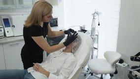 El cosmetólogo de la cámara lenta pone en el casquillo disponible en paciente antes del procedimiento cosmético, tratamiento almacen de metraje de vídeo