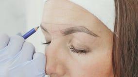El cosmetólogo de la muchacha marca con la ayuda de un lápiz el tatuaje futuro de cejas almacen de metraje de vídeo
