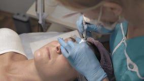El cosmetólogo del primer aplica el tatuaje alrededor de su frente del ` s del navegador almacen de metraje de vídeo