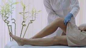 El cosmetólogo en el centro del balneario prepara las piernas de la mujer s para la depilación 4K metrajes