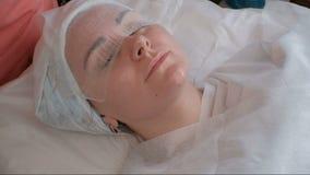 El cosmetólogo en guantes verdes pone un vendaje en la cara de una muchacha hermosa Preparación para el procedimiento de la aplic almacen de metraje de vídeo