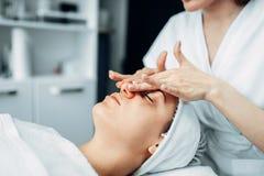 El cosmetólogo frota la crema en cara paciente femenina foto de archivo libre de regalías