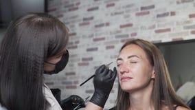 El cosmetólogo hace colorear las cejas del cliente almacen de video