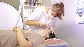 El cosmetólogo hace la corrección de las cejas de la goma del azúcar del cliente almacen de metraje de vídeo