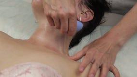 El cosmetólogo hace masaje antienvejecedor del cuello con los bancos del vacío masaje de cara del vacío para la regeneración de l almacen de video