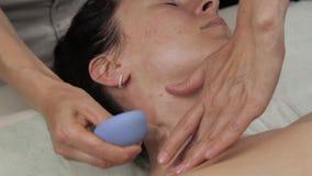 El cosmetólogo hace masaje antienvejecedor del cuello con los bancos del vacío masaje de cara del vacío para la regeneración de l metrajes