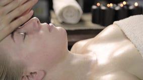 El cosmetólogo hace el masaje facial para la mujer hermosa en salón del balneario metrajes