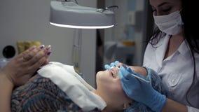 El cosmetólogo hace un limpiamiento del área de la nariz durante el procedimiento del limpiamiento facial mecánico almacen de metraje de vídeo