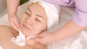El cosmetólogo limpia la piel y limpia los restos de la máscara cosmética de algas en el cuello y la cara de una muchacha asiátic metrajes