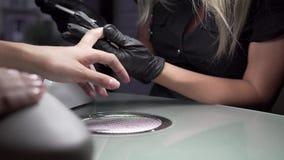 El cosmetólogo muele la barra de clavo para una manicura en el salón de belleza Tratamiento del clavo del finger, moliendo y puli almacen de video