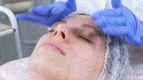 El cosmetólogo pone la crema en la cara de la mujer Tratamiento facial del Cosmetologist Primer almacen de metraje de vídeo