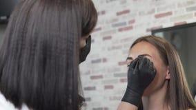 El cosmetólogo pone la pintura negra en las cejas del cliente en el salón de belleza almacen de video