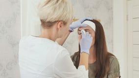 El cosmetólogo prepara las cejas del ` s del cliente para el tatuaje de la ceja Maquillaje permanente Tatuaje permanente de cejas almacen de metraje de vídeo