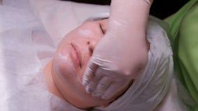 El cosmetólogo profesional en los guantes blancos pone una crema de alimentación en la cara de una mujer asiática Procedimiento c almacen de metraje de vídeo