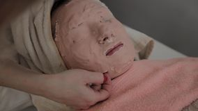 El cosmetólogo profesional quita la máscara de la cara de una chica joven Nuevo concepto en cosmetología almacen de metraje de vídeo
