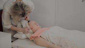 El cosmetólogo profesional quita la máscara de la cara de una chica joven Nuevo concepto en cosmetología almacen de video