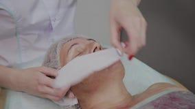 El cosmetólogo profesional quita trapos de la cara de una mujer mayor en la oficina de la cosmetología almacen de metraje de vídeo