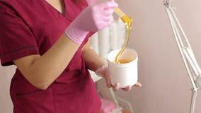 El cosmetólogo quita la goma del azúcar para encerar con un palillo de madera, azucarando almacen de metraje de vídeo