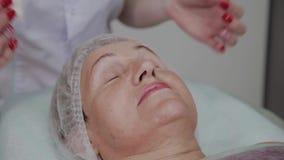 El cosmetólogo quita maquillaje a una mujer mayor en una clínica de la cosmetología metrajes