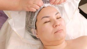 El cosmetólogo quita una toalla de la cabeza de una mujer asiática Primer de manos y de la cara femeninas en un centro de la cosm metrajes