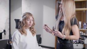 El cosmetólogo sonriente precioso que usa el cepillo en clientes hace frente en un salón de belleza almacen de video