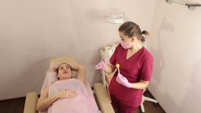 El cosmetólogo toma la goma del azúcar de los bancos para la depilación de los axilas de la mujer metrajes