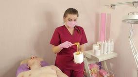El cosmetólogo toma la goma del azúcar de los bancos para la depilación del pecho masculino almacen de metraje de vídeo