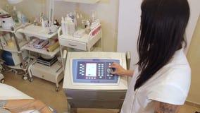 El cosmetólogo trabaja en el aparato del biostimulation que hace la muchacha un masaje almacen de video