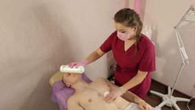 El cosmetólogo vierte el talco en sirve el pecho antes del procedimiento del epilation almacen de metraje de vídeo