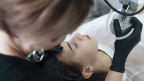 El cosmet?logo de la c?mara lenta hace la peladura facial del laser para la mujer con el dispositivo especial almacen de video