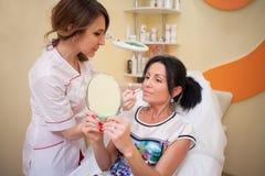 El cosmetolog del doctor muestra un problema de la mujer en balneario de la cara Fotografía de archivo