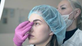 El Cosmetologist comprueba la frente fresca que tat?a en cara del cliente metrajes