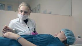 El Cosmetologist con el cliente elige el color para el tatuaje de la frente almacen de video