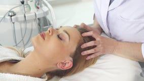 El Cosmetologist da masajes a la cabeza del ` s del cliente almacen de metraje de vídeo