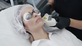 El cosmetologist de la cámara lenta hace el procedimiento de la muchacha para curar la piel de la cara con el dispositivo especia almacen de video