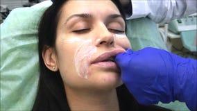 El cosmetologist del dermatólogo del doctor realiza masaje de los labios después de plástico del contorno almacen de video