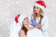 El cosmetologist del doctor hace la inyección en la piel de la cara y los labios de una mujer hermosa, joven en el sombrero de Sa fotos de archivo